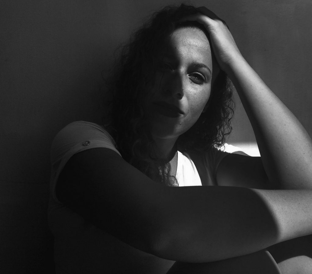 grayscale-photo-of-woman-leaning-on-wall-2229502